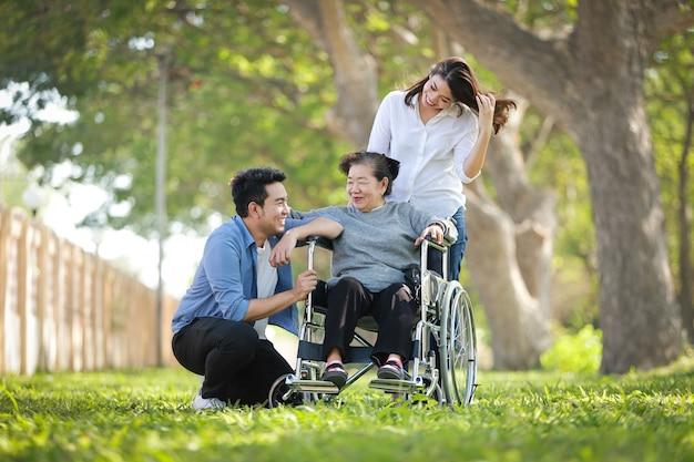 Azjatycki starszy kobiety obsiadanie na wózku inwalidzkim z rodzinną szczęśliwą uśmiech twarzą na zielonym parku