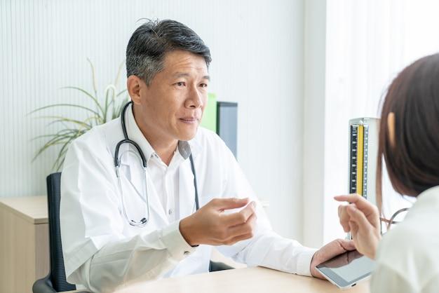 Azjatycki starszy lekarz i pacjent dyskutują