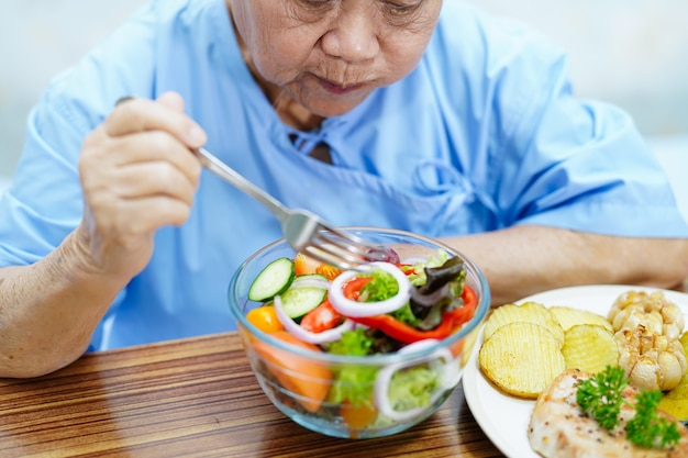 Azjatycki starszy lub starszy pacjentka starsza pani jedzenie śniadanie warzyw zdrowej żywności z nadzieją i szczęśliwy, siedząc i głodny na łóżku w szpitalu.