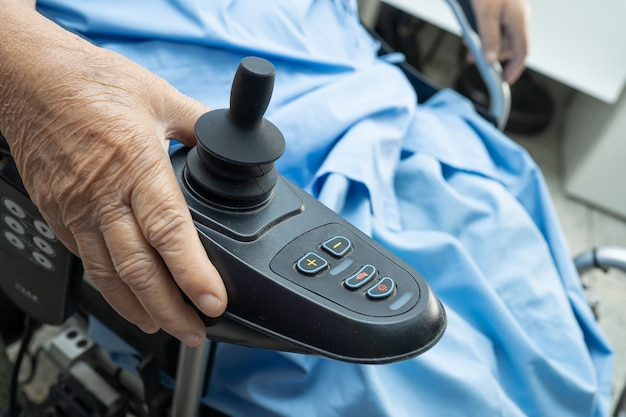 Azjatycki starszy lub starszy pacjentka staruszka na elektrycznym wózku inwalidzkim z pilotem na oddziale szpitala pielęgniarskiego, zdrowa, silna koncepcja medyczna