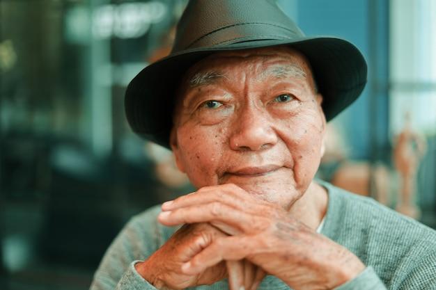 Azjatycki starszy mężczyzna pije kawę w sklep z kawą kawiarni