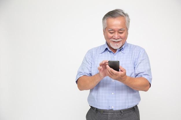 Azjatycki starszy mężczyzna za pomocą smartfona na białym tle nad białą ścianą