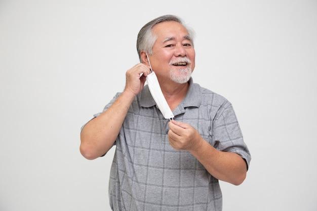 Azjatycki starszy mężczyzna zdejmuje maskę ochronną na białym tle