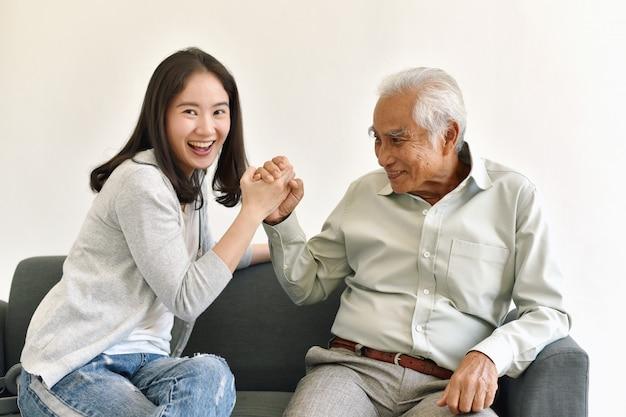 Azjatycki starszy ojciec ma zabawę z uśmiechniętą córką, starszy tata spędza czas z szczęśliwą rodziną.