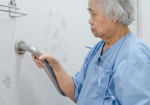 Azjatycki starszy pacjent korzysta z toalety w łazience z zabezpieczeniem w szpitalu pielęgniarskim
