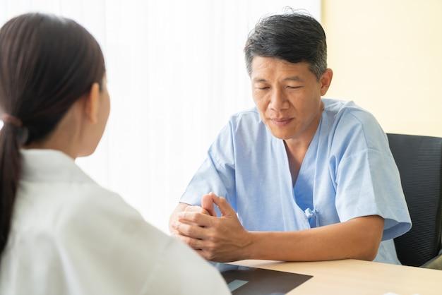 Azjatycki starszy pacjent ma konsultację z lekarką w biurze