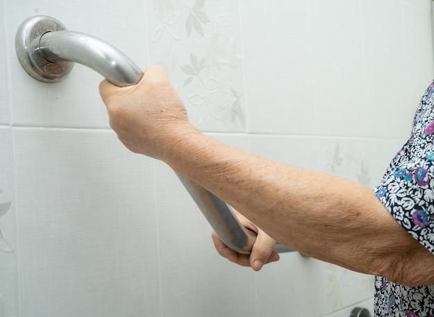 Azjatycki starszy pacjent pacjent używa toalety łazienka uchwyt bezpieczeństwa w szpitalu