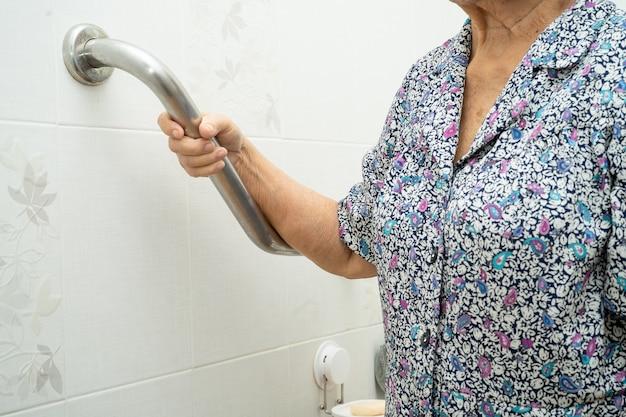 Azjatycki starszy pacjent pacjent używa toalety uchwyt bezpieczeństwa w szpitalu