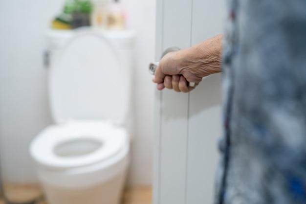 Azjatycki starszy pacjent pacjenta otwarta toaleta łazienka.