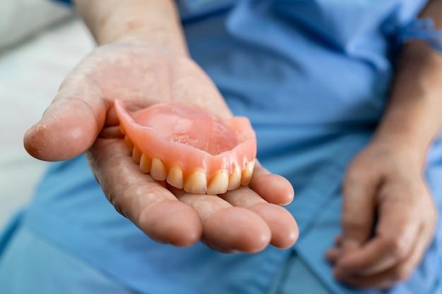 Azjatycki starszy pacjent pacjenta trzymając protezę w szpitalu.