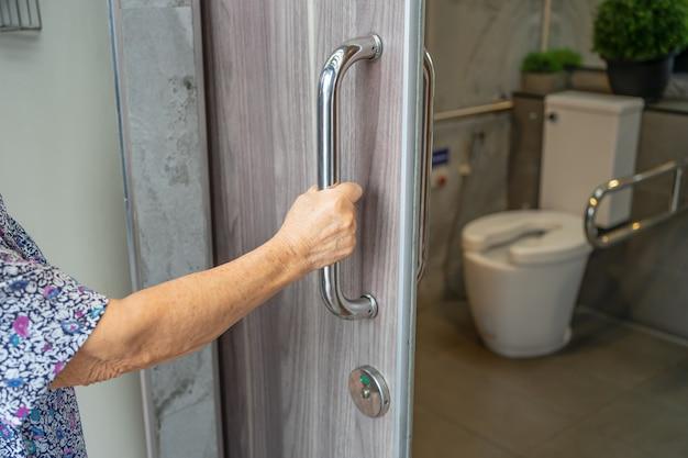 Azjatycki starszy pacjent używa toalety łazienka uchwyt bezpieczeństwa.