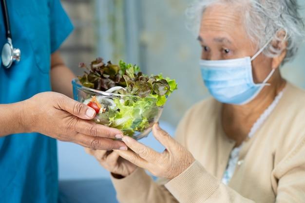 Azjatycki starszy pacjentka kobieta z maską gospodarstwa zdrowej żywności warzyw w szpitalu
