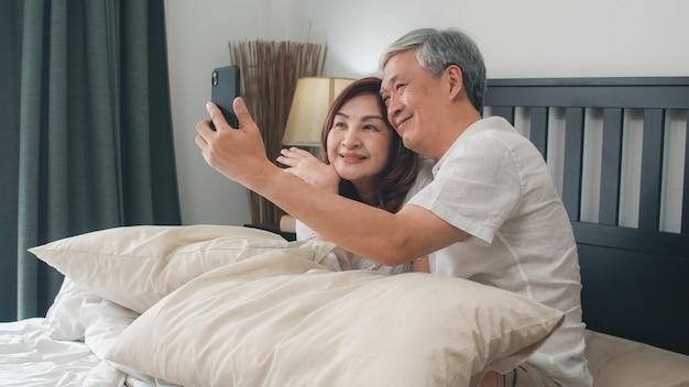 Azjatycki starszy pary selfie w domu. azjatyccy starsi chińscy dziadkowie, mąż i żona szczęśliwi używa telefonu komórkowego selfie po, budzili się kłamać na łóżku w sypialni w domu w ranku pojęciu.