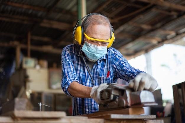 Azjatycki starszy stolarz nosi maskę higieniczną, chroniąc powierzchnię za pomocą strugarki elektrycznej na drewnianej desce w warsztacie stolarskim