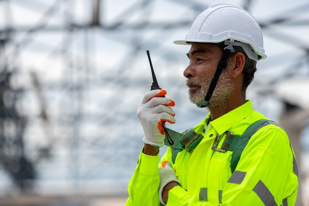 Azjatycki starszy technik inżynier nadzorujący kontrolę budowy przy budowie konstrukcji dachowych na budowie