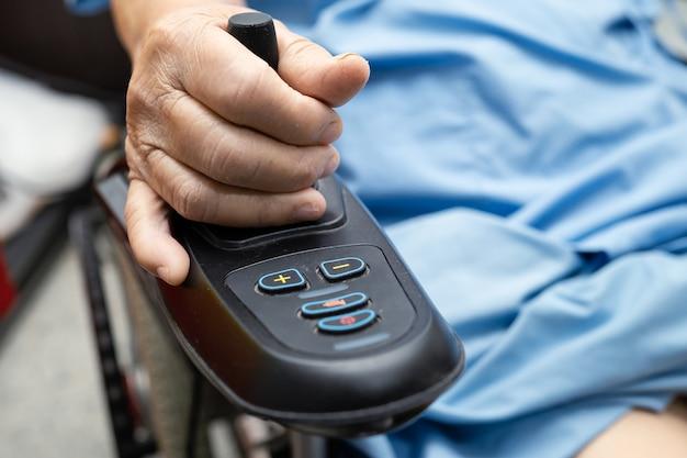 Azjatycki starszych lub starszych staruszka pacjentka na elektrycznym wózku inwalidzkim z pilotem na oddziale szpitala pielęgniarskiego