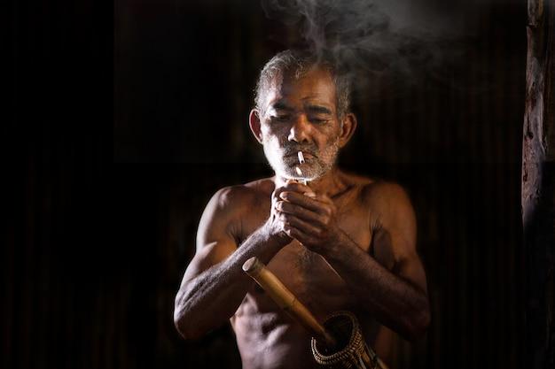 Azjatycki starzec pali papierosa, az ust wydobywa się dym w ciemności