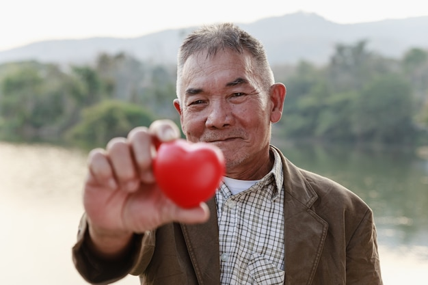 Azjatycki starzec uśmiecha się i pokazuje czerwone serce, walentynki i starszy zdrowy koncepcja.