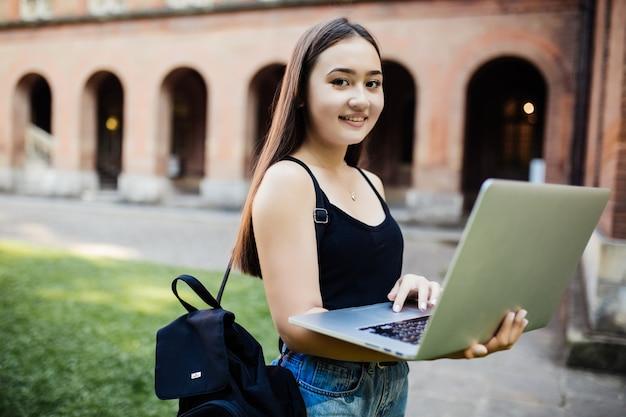 Azjatycki studencki działanie z komputerowego laptopu kampusu zieleni parka plenerowym uniwersyteckim pojęciem