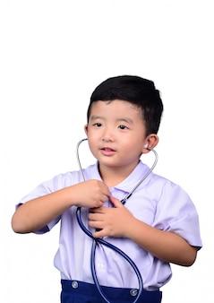 Azjatycki studencki dzieciak w mundurku szkolnym bawić się medycznego stetoskop odizolowywającego