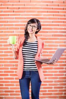 Azjatycki student collegu z laptopem i kawą
