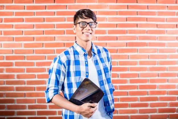 Azjatycki student collegu z pastylka komputerem