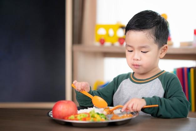 Azjatycki student je obiad w klasie przy tacy z jedzeniem przygotowanej przez jego przedszkole