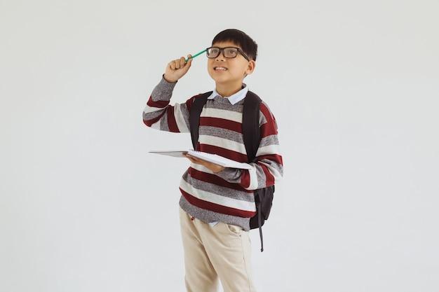 Azjatycki student trzymający książkę stojąc i myśląc