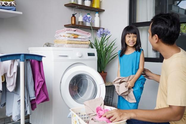 Azjatycki szczęśliwy człowiek rodziny ojciec gospodarstwa domowego i córka dziecko w pralni z pralką razem