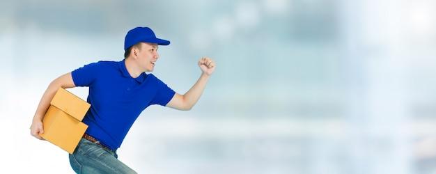 Azjatycki szczęśliwy doręczeniowy mężczyzna jest ubranym błękitnego koszulowego bieg i niesie papierowych pakuneczek boksuje odosobnionego na plamy okno.
