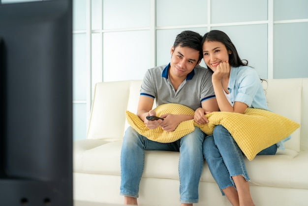 Azjatycki szczęśliwy fcouple siedzi w kanapie i ogląda telewizję w domu