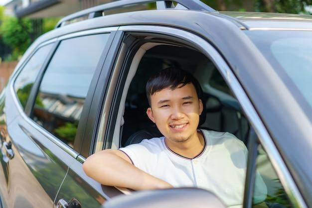 Azjatycki szczęśliwy młody przystojny mężczyzna prowadzący samochód na przednim siedzeniu z uśmiechem przygotowuje się do podróży swoim samochodem.