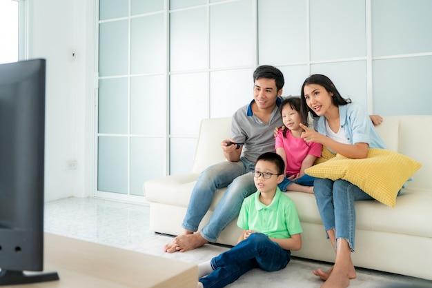Azjatycki szczęśliwy rodzinny obsiadanie w kanapie i oglądać telewizję w domu
