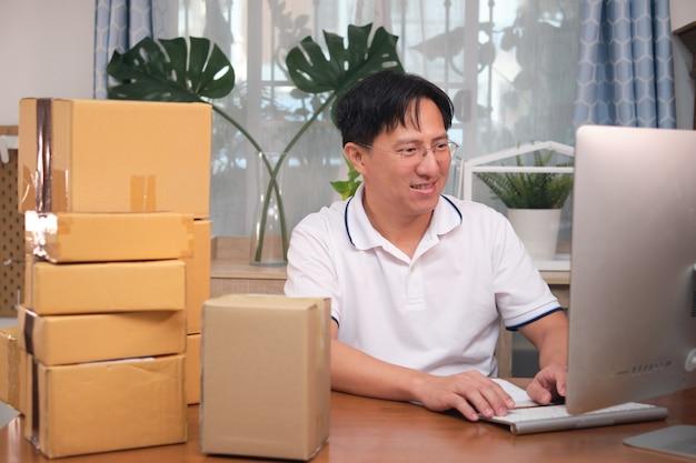 Azjatycki szczęśliwy uśmiechnięty biznesmen przedsiębiorca za pomocą komputera