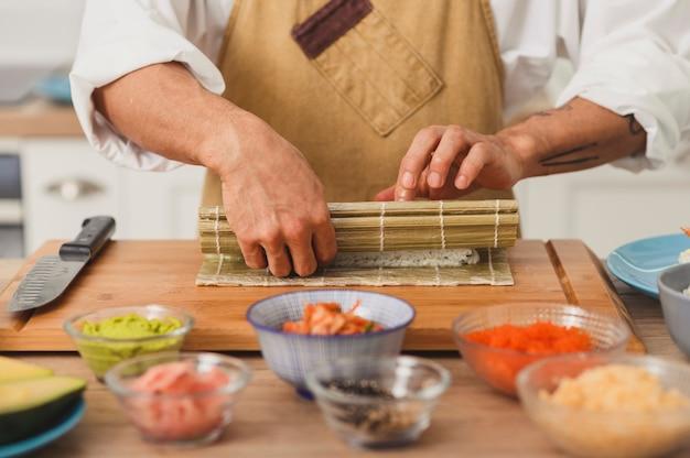 Azjatycki szef kuchni wręcza toczenie sushi z maty bambusowej proces przygotowania sushi ze składnikami potraw z japonii