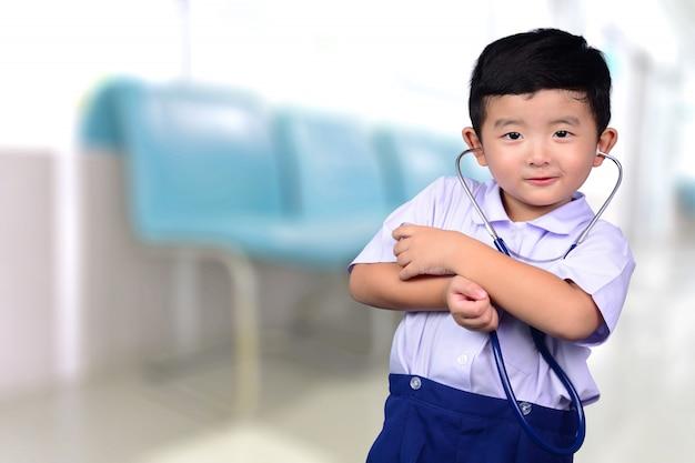Azjatycki tajlandzki dzieciak patrzeje kamerę z medycznym stetoskopem, zdrowy pojęcie.