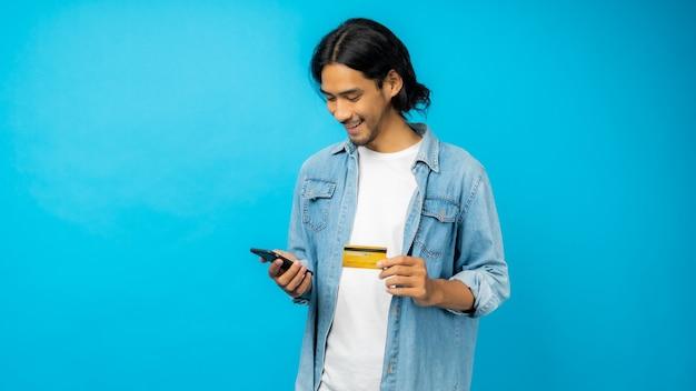 Azjatycki tajski mężczyzna z długimi włosami i wąsami, trzymając telefon z kartą kredytową, zakupy online koncepcja na niebieskim tle