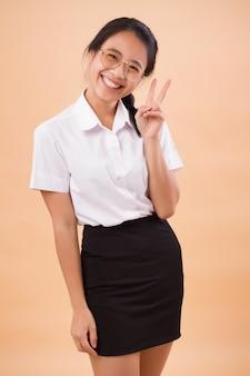 Azjatycki tajski studentka college'u w mundurze. portret szczęśliwy uśmiechający się studentka azjatyckiego tajskiego uniwersytetu