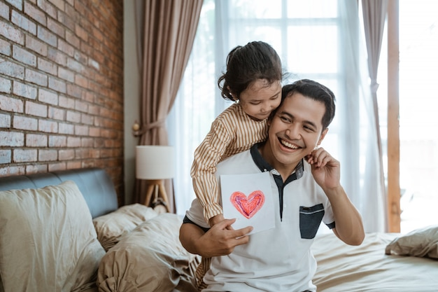 Azjatycki tata uśmiecha się, gdy jest przytulany przez córeczkę od tyłu, trzymając papier z sercem
