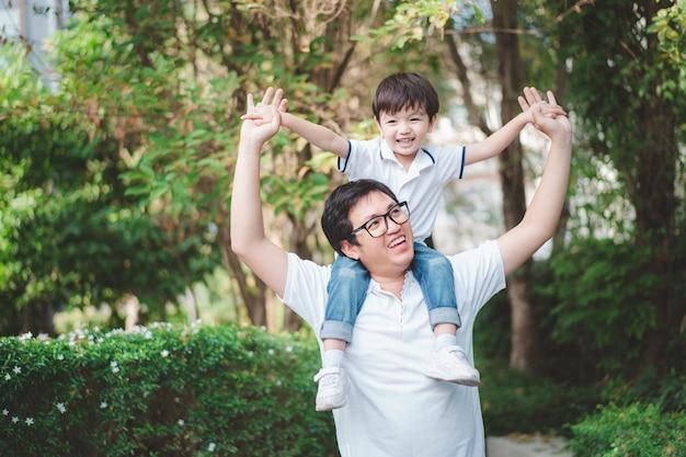 Azjatycki tatuś zabiera syna bawiącego się po parku