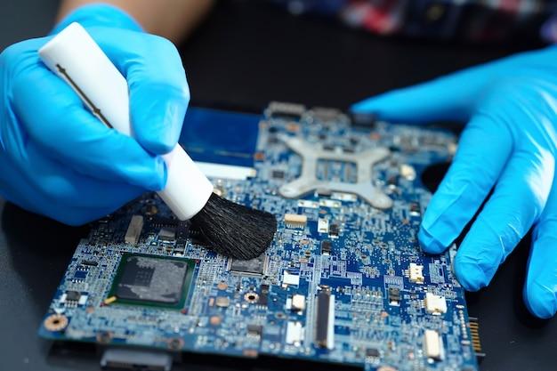 Azjatycki technik naprawia i czyści brudną mikroelektroniczną płytę główną elektroniczną techniką komputerową za pomocą pędzla.