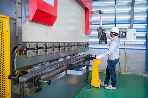Azjatycki technik robotnik kontrolujący maszynę