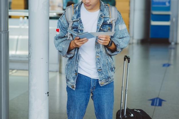 Azjatycki turysta mężczyzna posiadający paszport i bilet lotniczy