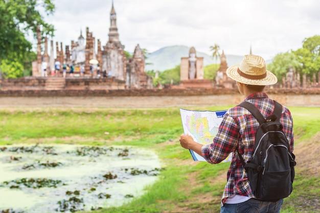 Azjatycki turystyczny mężczyzna w sukhothai dziejowym parku, tajlandia