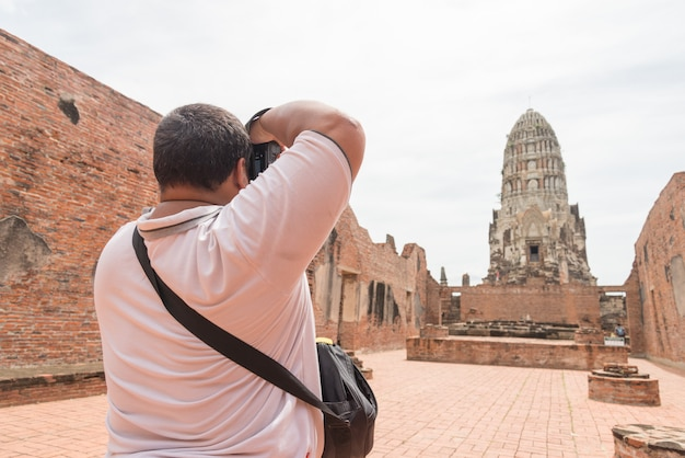 Azjatycki turystyczny mężczyzna z tłuszczem robi fotografii antyczna pagoda jest buddyjską świątynią