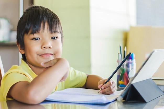 Azjatycki uczeń chłopiec używający i dotykający inteligentnego tabletu lub tabletu do odrabiania lekcji