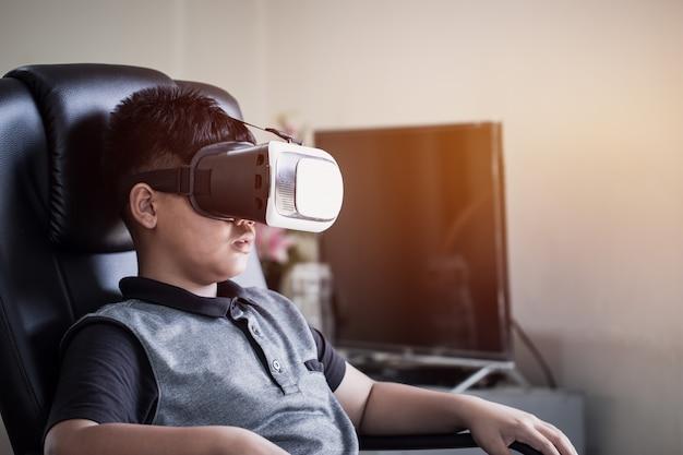 Azjatycki uczeń jest ubranym słuchawki wirtualnej rzeczywistości nad technologia cyfrowym wirtualnym piargiem