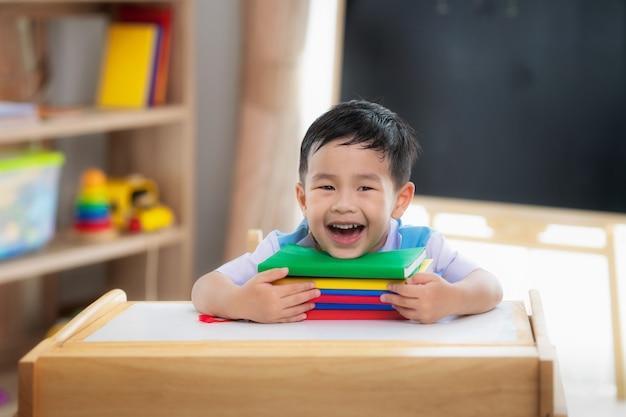 Azjatycki uczeń szczęśliwy po powrocie do szkoły i uśmiechu w swojej klasie w przedszkolu, ten obraz może być użyty do koncepcji edukacji, ucznia, szkoły i stylu