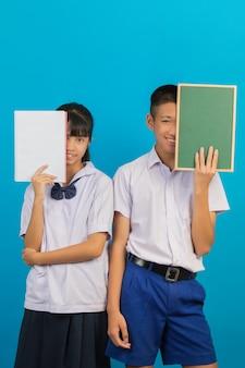 Azjatycki uczeń trzyma notatnika i azjatycki męski uczeń trzyma zieloną deskę na błękicie.