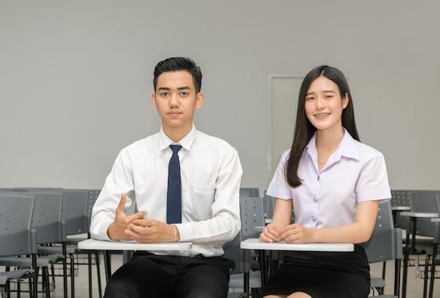 Azjatycki uczeń z nawiasami klamrowymi na zębach i przyjacielem w sala lekcyjnej